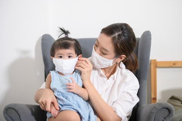 アジアのママと娘は防護マスクを着ています