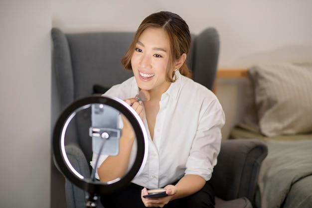 美しいアジアのメイクアップブロガーが自宅で顔メイクを美容する方法をライブストリーミングしています