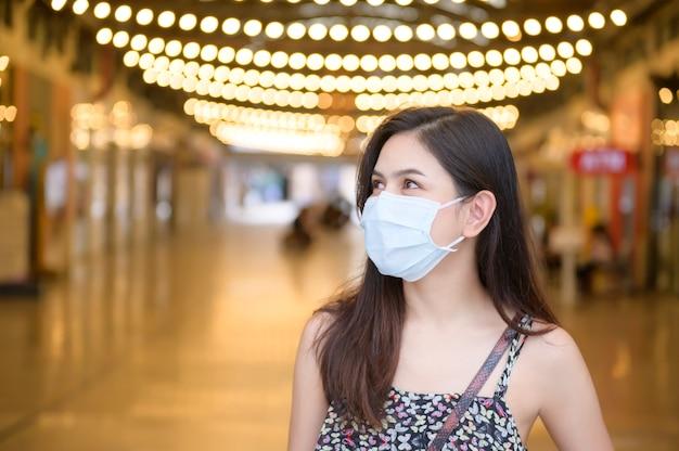 若いアジアの女性がショッピングセンターで買い物防護マスクを着ています。