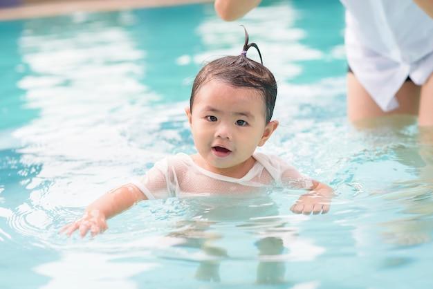 幸せなアジアの母と娘は、プール、ライフスタイル、親子関係、家族の概念で水泳を楽しんでいます。