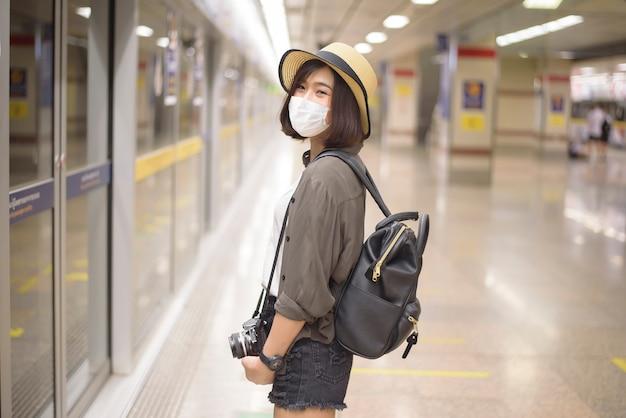 若いかなりアジアの女性は地下鉄の駅に立っている防護マスクを着ています。