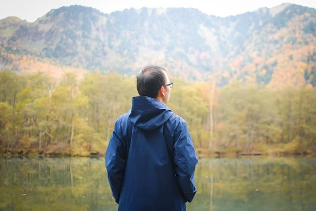 Человек свободы стоит на берегу озера против естественного осеннего леса и гор