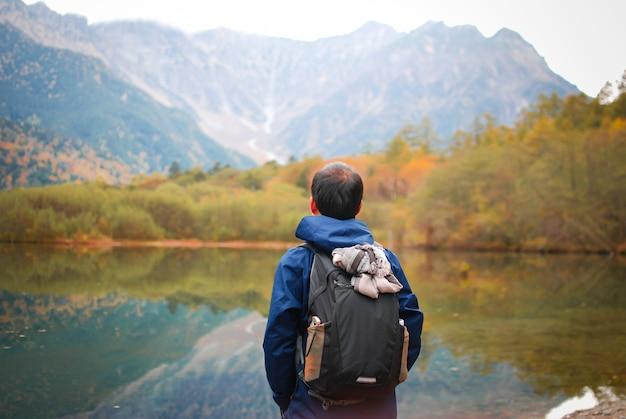 Свобода человека с поднятыми руками на берегу озера против естественного осеннего леса и гор