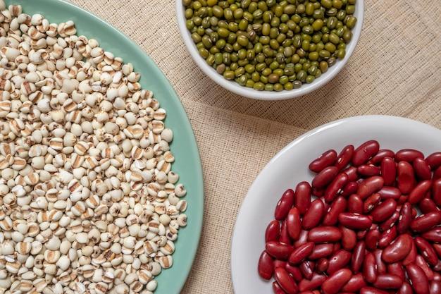 写真は様々な全粒穀物、インゲン、小豆、皿のキビ、茶色のテーブルクロス、木目、食品広告に適しています。