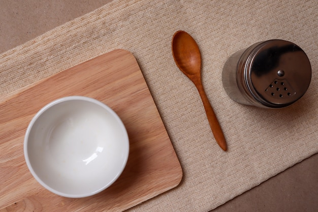 クリームテーブルクロスに白い皿と木のスプーンとスパイスの瓶を食べる準備ができて
