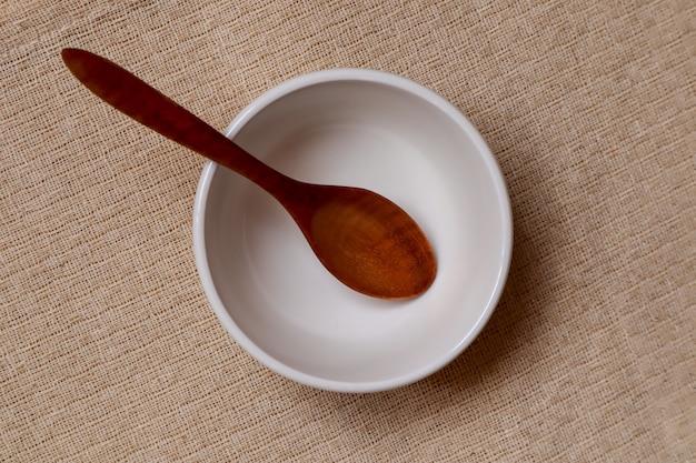 白いプレートとクリームテーブルクロスに木のスプーンを食べて準備ができて