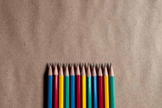 茶色の紙の上の多くのカラフルな鉛筆はデザインに適用することができます。