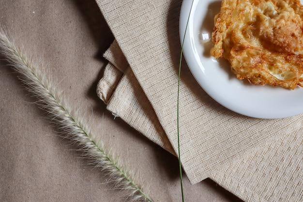 Омлет в белом блюде, который помещают на светло-коричневую ткань и траву для красоты