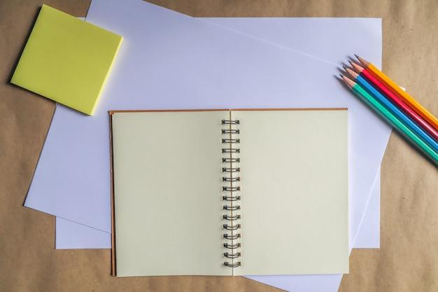 Разноцветные карандаши и коричневые тетради на белом фоне