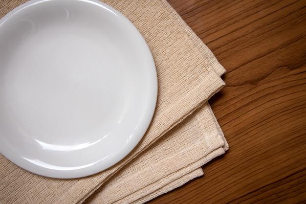 白い皿は木製のテーブルの上のクリーム色のテーブルクロスの上に置かれます。