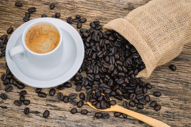 Кофейная чашка и кофейные зерна зажарили в духовке в мешке на деревянном поле.