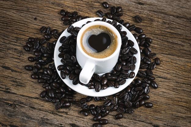 Кофе сердца и кофейные зерна зажарили в духовке в мешке на деревянном поле.