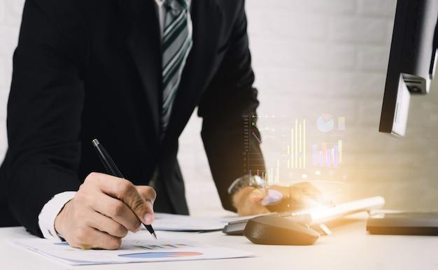 ビジネスの男性はテーブルで作業しますドキュメントとコンピューターでグラフ財務レポートを分析します。