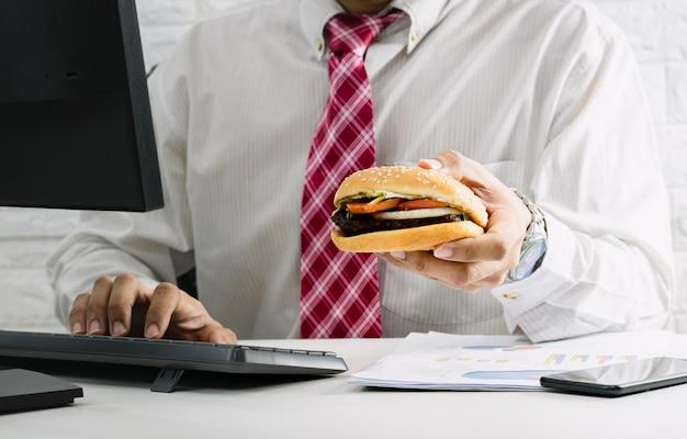 働く男性はオフィスで働いている間ジャンクフードのハンバーガーを緊急に食べる時間がない