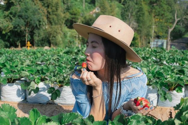 女性はフルーツ農家でイチゴを食べる。
