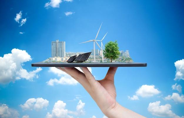 タブレットを持っている手に都市の生態系太陽エネルギー