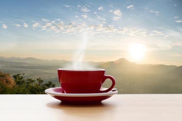 Кофейная чашка красная с утренним солнцем горы