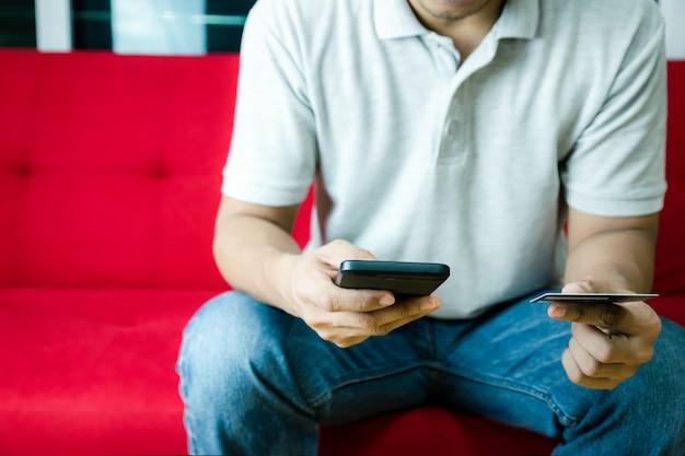 男の手持ち株ショッピングとクレジットカードは、スマートフォンを使用してオンライン支払いを管理します。
