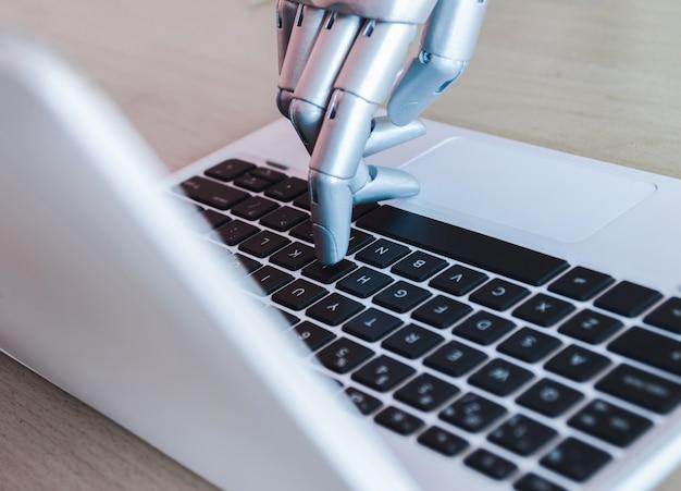 ロボットの手と指がノートパソコンのボタンアドバイザーを指す