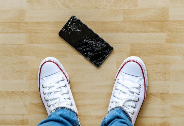 人々は床の壊れた画面にスマートフォンを落ちる