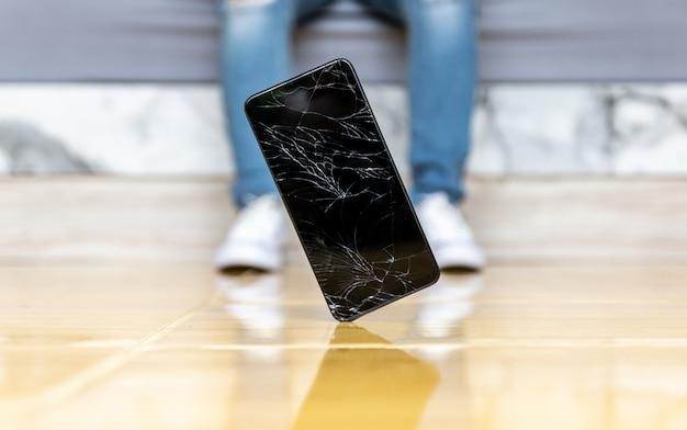 Люди опускают смартфон на пол разбитого экрана