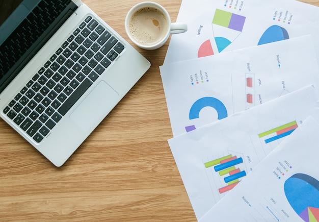 ビジネスでの机上の分析とラップトップ上のグラフ