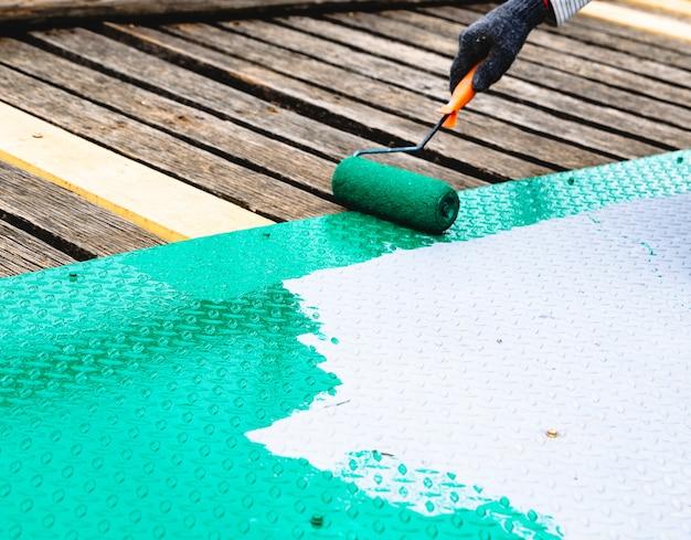 スチールの床にローラーで塗装