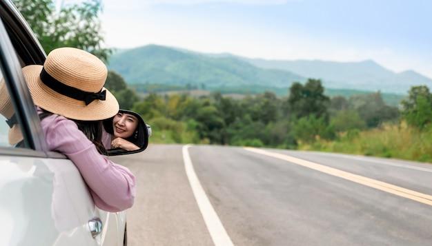 道路上の運転の女性が車で旅行をリラックスします。