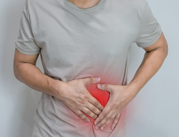 腹部の痛みや怪我を示すために胴回りの両方の手のひらで胃の痛みに苦しんでいる男性