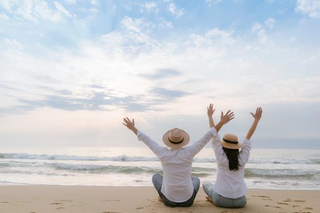 男性と女性はビーチで幸せな休日のリラックスした日に旅行します。