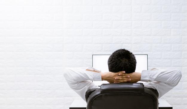 コンピューターを見て、仕事でリラックスして満足している男性。