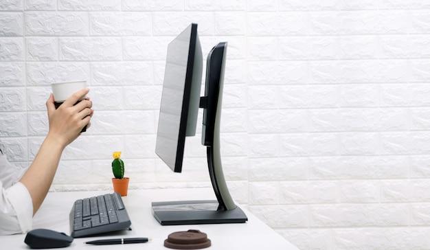 仕事の机の上にコーヒーカップを持って働くオンラインビジネスをリラックスします。