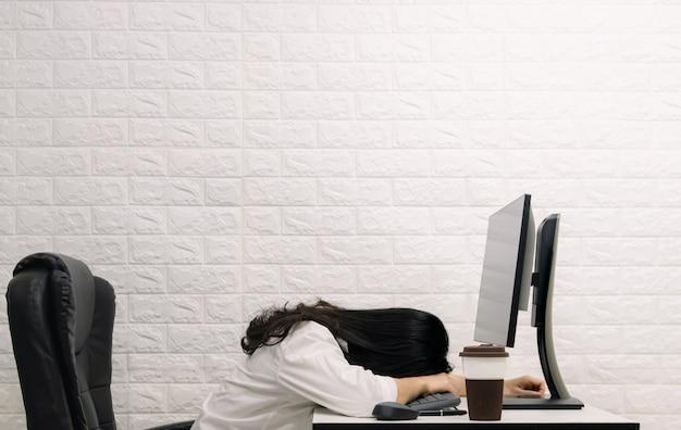 机の上で寝ている女性コンピューターの画面