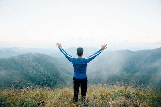幸せな男の後部はドイランカルアン、チェンライ県で霧と雲の景色を見ている山の上に立ちます。ソフトフォーカス