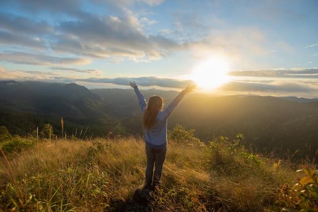 幸せな女の後部は、チェンライ県ドイランカルアンで日の出と霧の景色を見ている山の上に立ちます。ソフトフォーカス