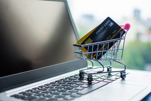 ショッピングカートとコンピューターのオンラインショッピングのクレジットカード。