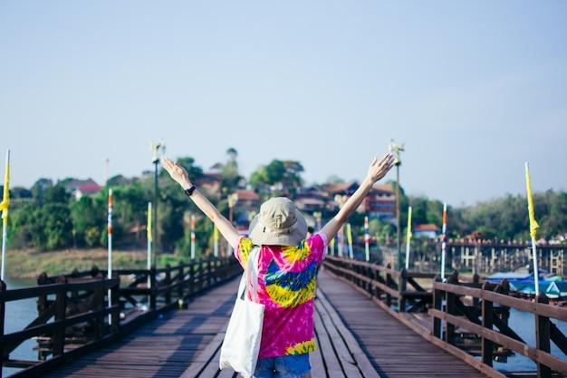 女性の後部は旅行し、カンチャナブリーで木の月橋の上に立ちます。
