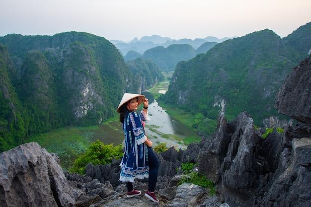 幸せな女は夕方、ベトナムのニンビン、ムア洞窟の山の頂上に立って、被写体はぼやけて、低キーとノイズです。