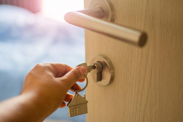 朝の光、個人ローンでドアの人間の手タッチキーを閉じます。被写体がぼやけています。
