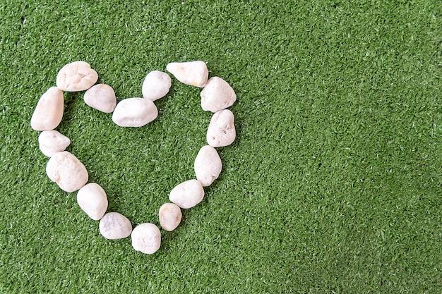 Белые камни в форме сердца на зеленом траве для любви