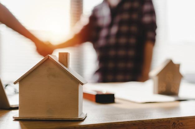 パートナーシップ。職場の机の上の木造住宅モデル