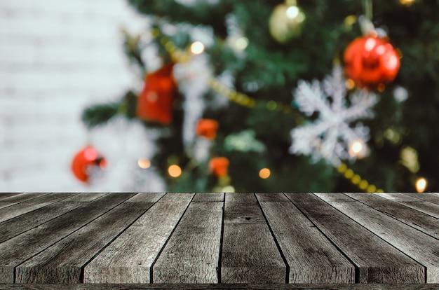 空の灰色の木製テーブルまたはクリスマスの背景に掛かっている装飾が施されたボールの画像がぼやけて木製テラス