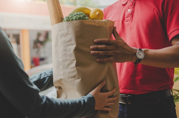 Умный человек службы доставки еды в красной форме вручает свежие продукты получателю и клиенту молодой женщины, получающей заказ от курьера на дому