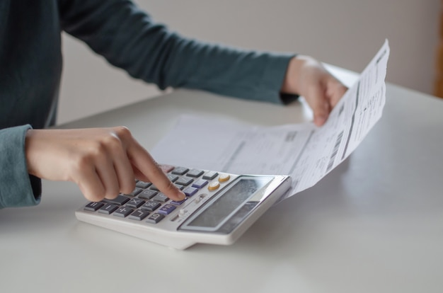 Молодая женщина, используя калькулятор для анализа и расчета семейного бюджета счета расходы отчет на столе в домашнем офисе