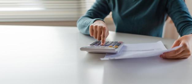 パノラマバナー。ホームオフィスの机の上の家族の予算費用の請求書を計算するための計算機を使用して若い女性の手