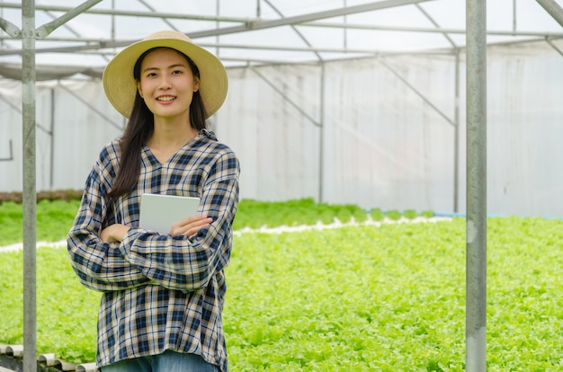 笑みを浮かべて、水耕栽培の新鮮な緑の野菜とモバイルスマートタブレットを保持しているアジアの若いフレンドリーな女性農民が温室の庭の保育園で生産します。