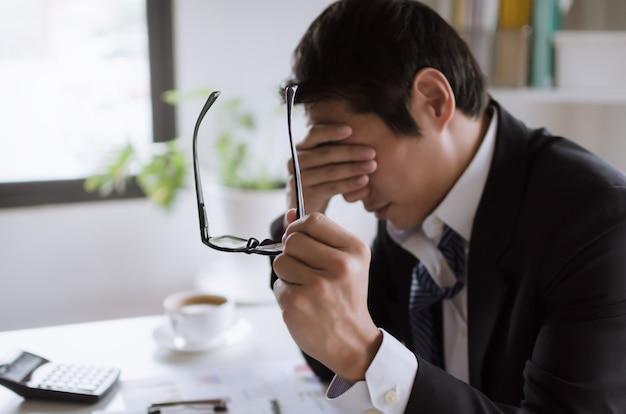 コンピューター、過労、オフィスシンドローム、ビジネス上の問題、金融の概念での長時間のオフィス作業の後、ストレスを感じて眼鏡を脱いで疲れたアジア青年実業家が眼精疲労を感じる