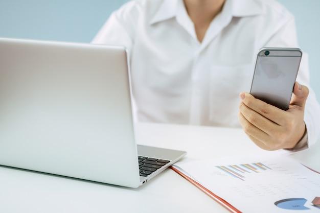 スマートフォン、ラップトップ、ビジネス戦略レポートドキュメントの操作
