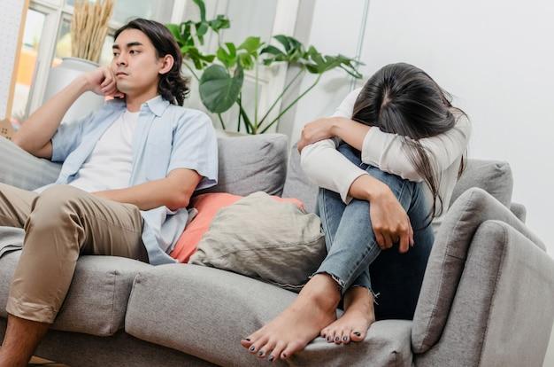 けんかをして、戦いの後ソファーに座っていた悲しみ若いアジアの妻