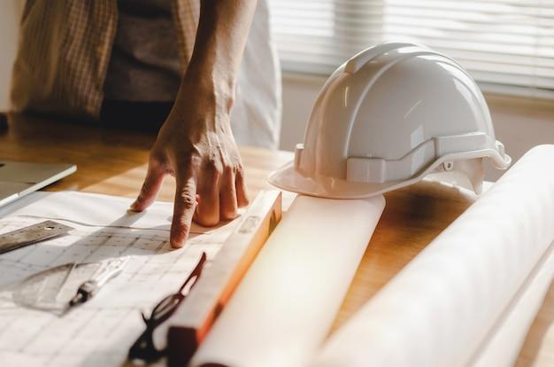 プロの建築家、エンジニアまたは職場の机の上の青写真と一緒にインテリア計画建設